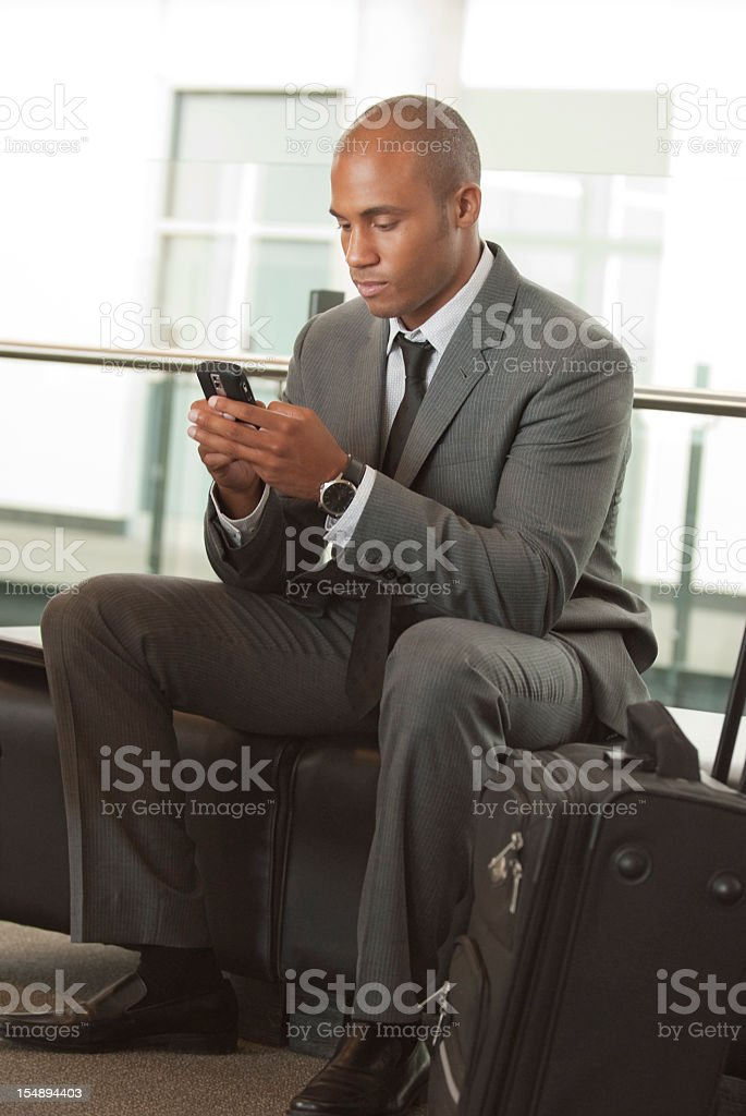 Businessman texting from his smartphone in an airport royalty-free stock photo