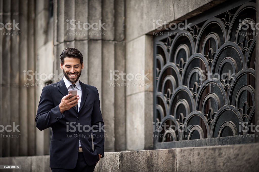 Businessman texting messages while walking stock photo
