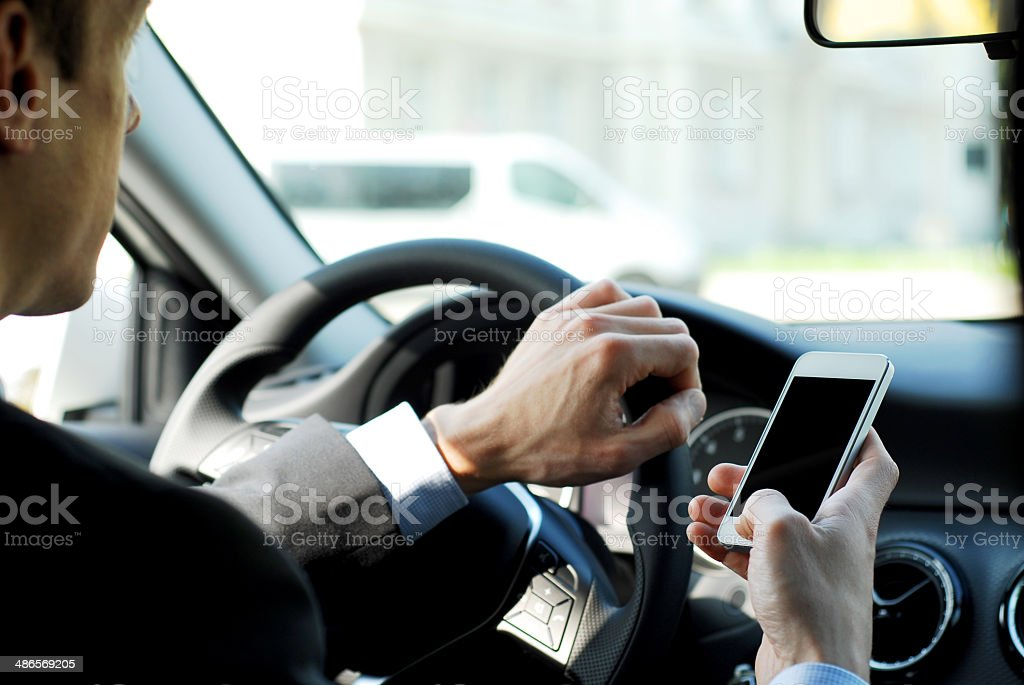 Businessman texting while driving a car stock photo