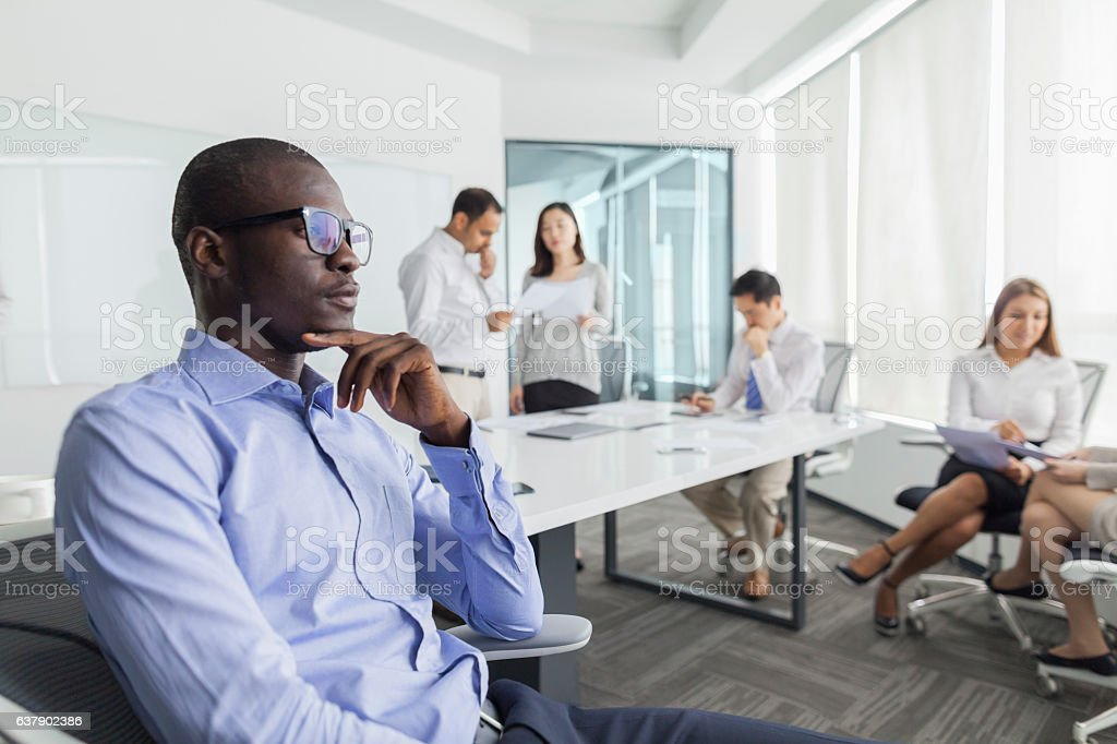 Businessman thinking during meeting in office stock photo