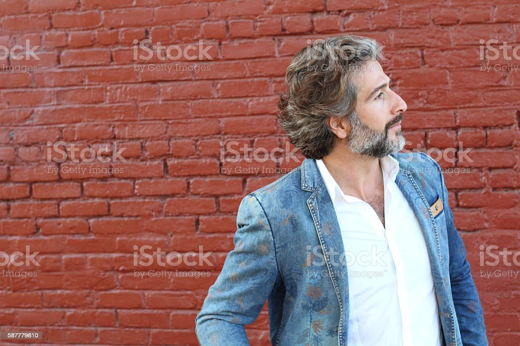 Businessman thinking in front of red wall stock photo