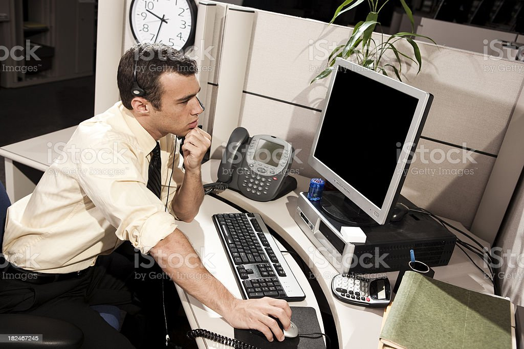 Businessman Thinking in Office Cubicle WHile Working on COmputer stock photo