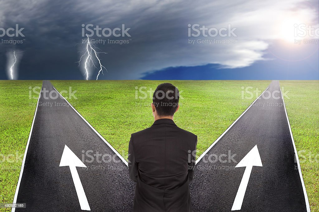 Businessman thinking to choice in between thunder and sunny way stock photo