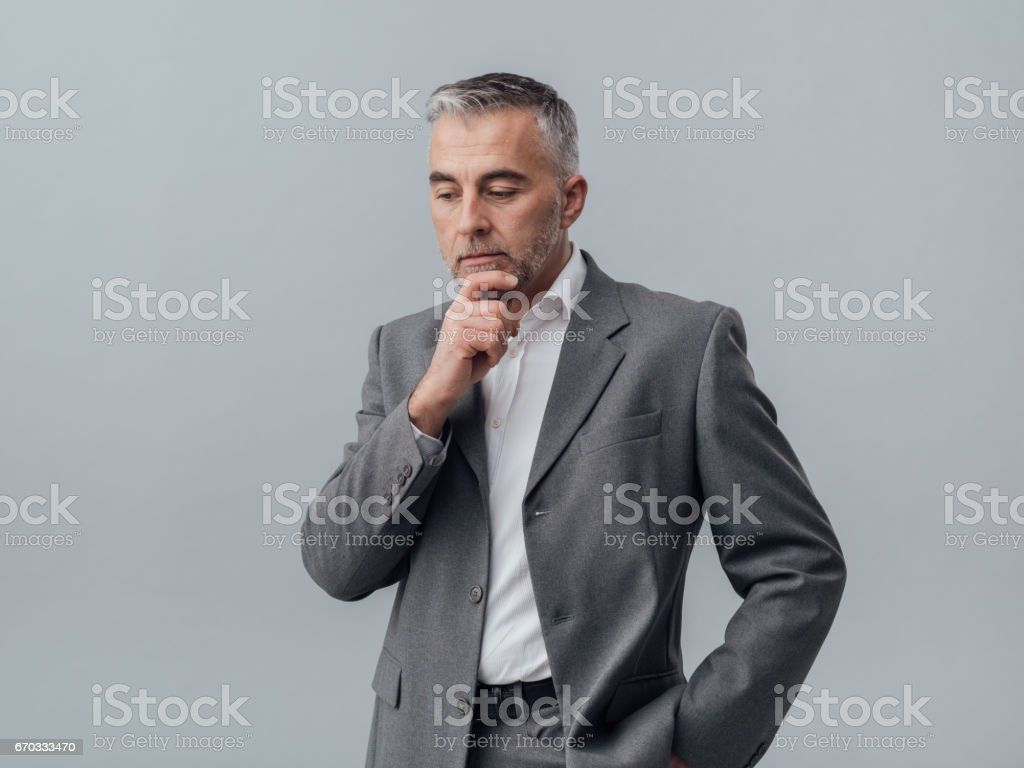 Businessman thinking with hand on chin stock photo