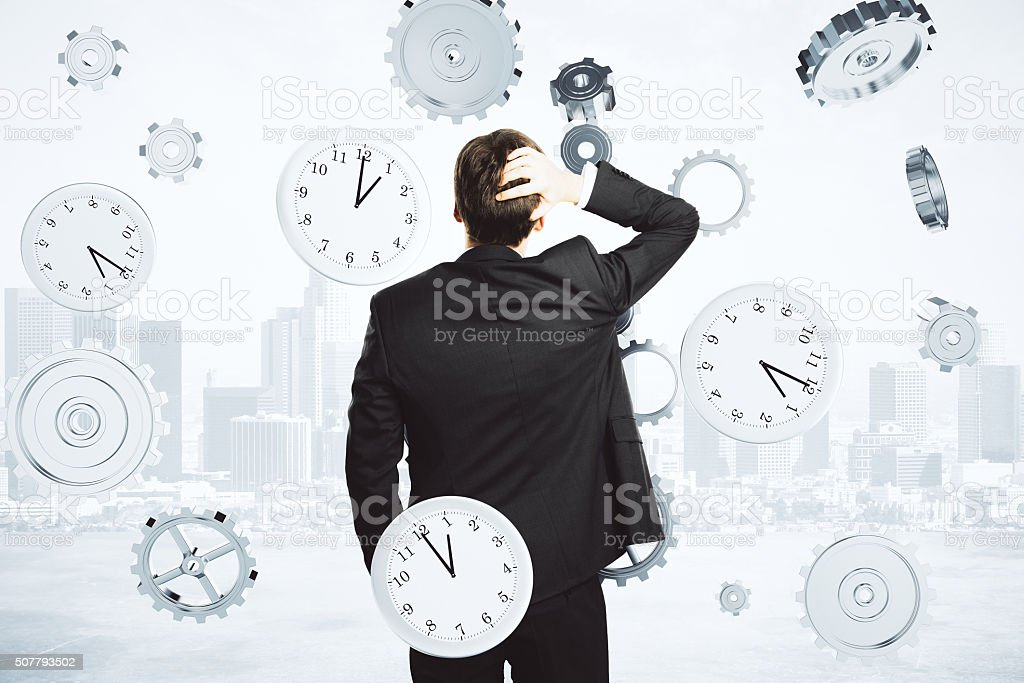 Businessman thinks about the time surrounded by clock and gears stock photo