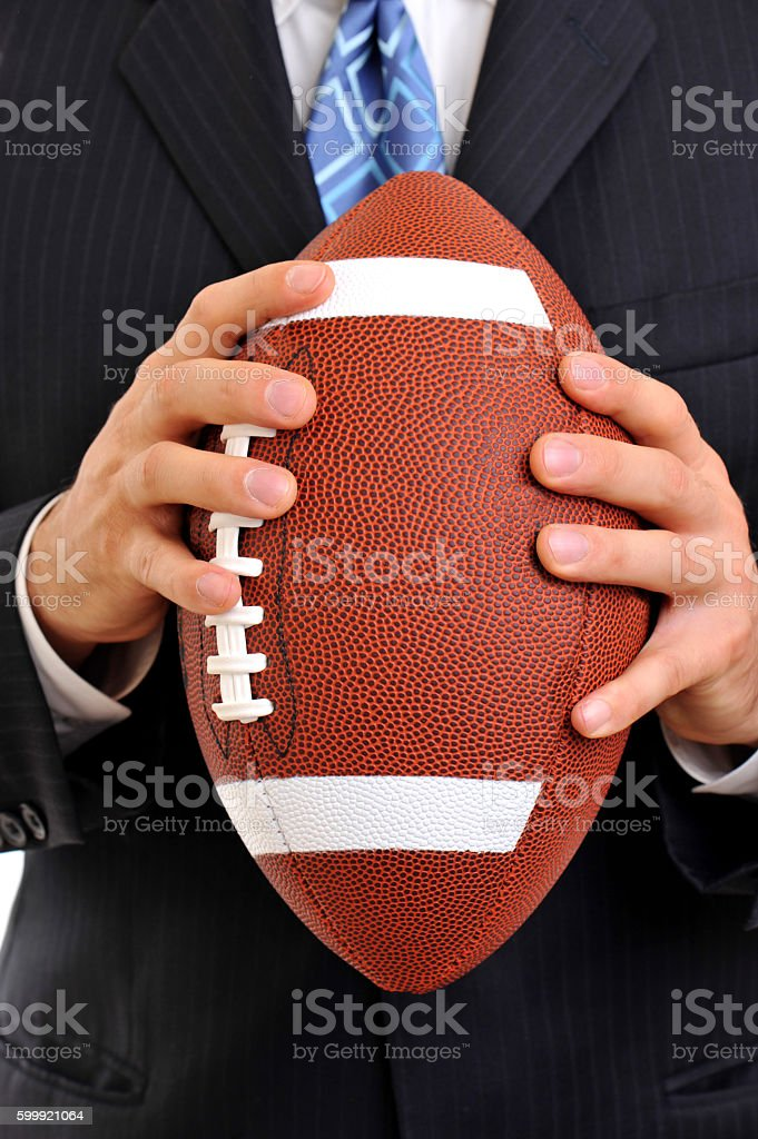 Businessman Throwing American Football on White stock photo
