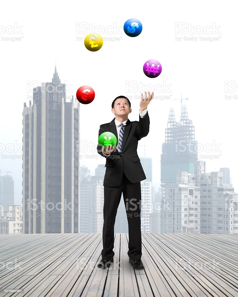 businessman throwing and catching currency symbol balls stock photo