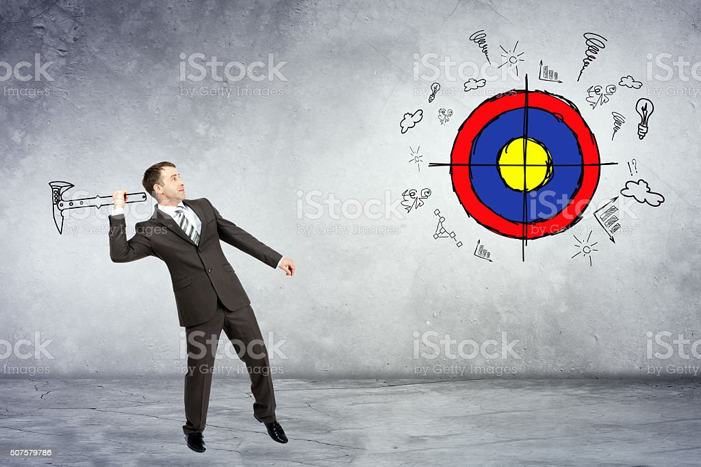 Businessman throwing axe to darts stock photo