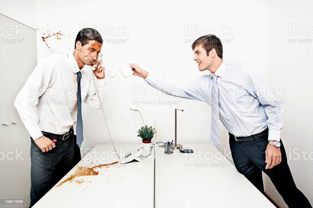 businessman throwing coffee to his colleague stock photo