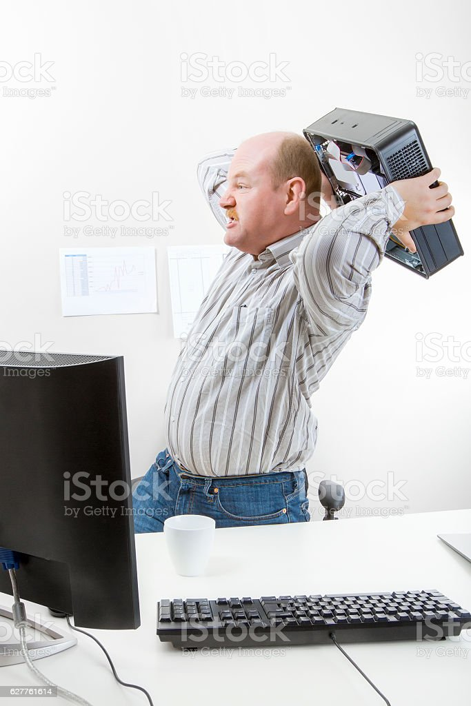 Businessman Throwing Computer Chassis By Desk stock photo