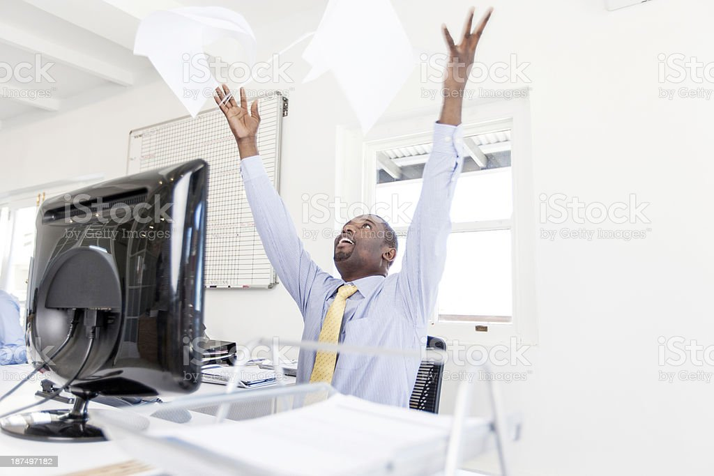 Businessman throwing his paperwork in the air with joy! stock photo