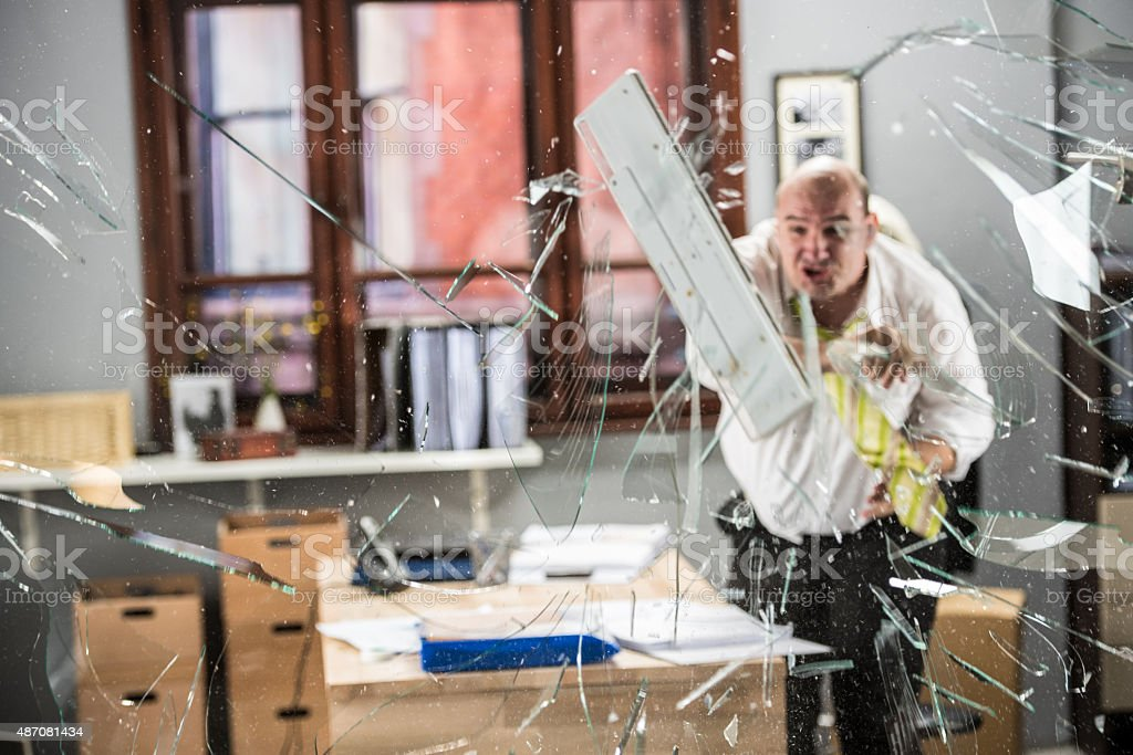 Businessman throwing keyboard on glass stock photo