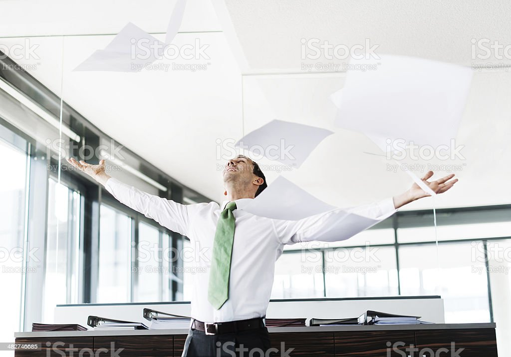 Businessman Throwing Paper In Office stock photo