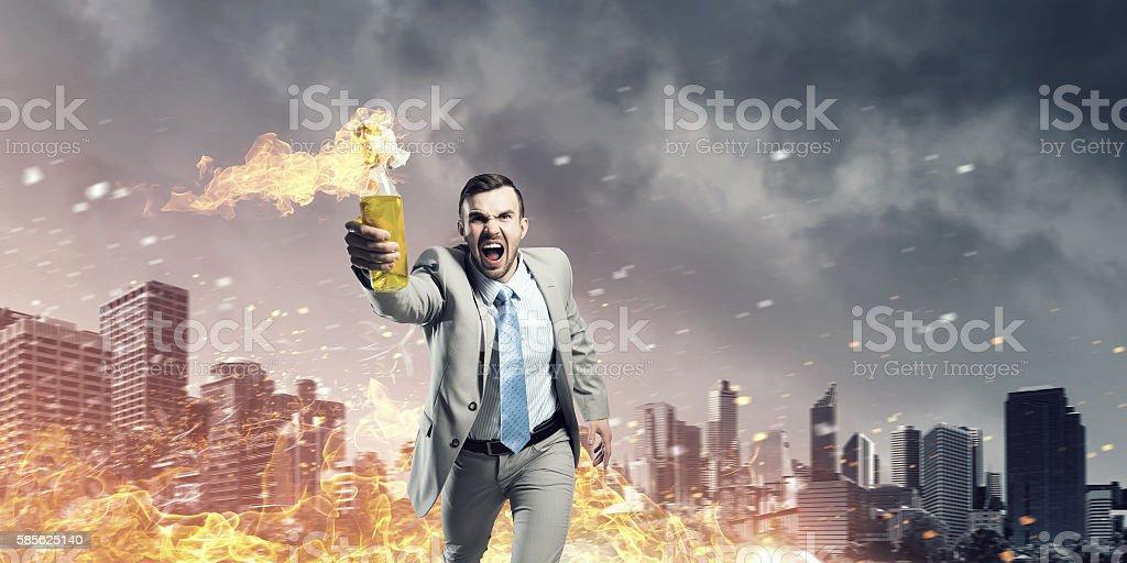 Businessman throwing petrol bomb . Mixed media stock photo