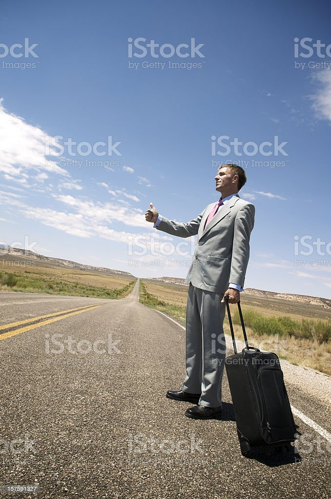 Businessman Thumbs a Ride on Endless Highway royalty-free stock photo