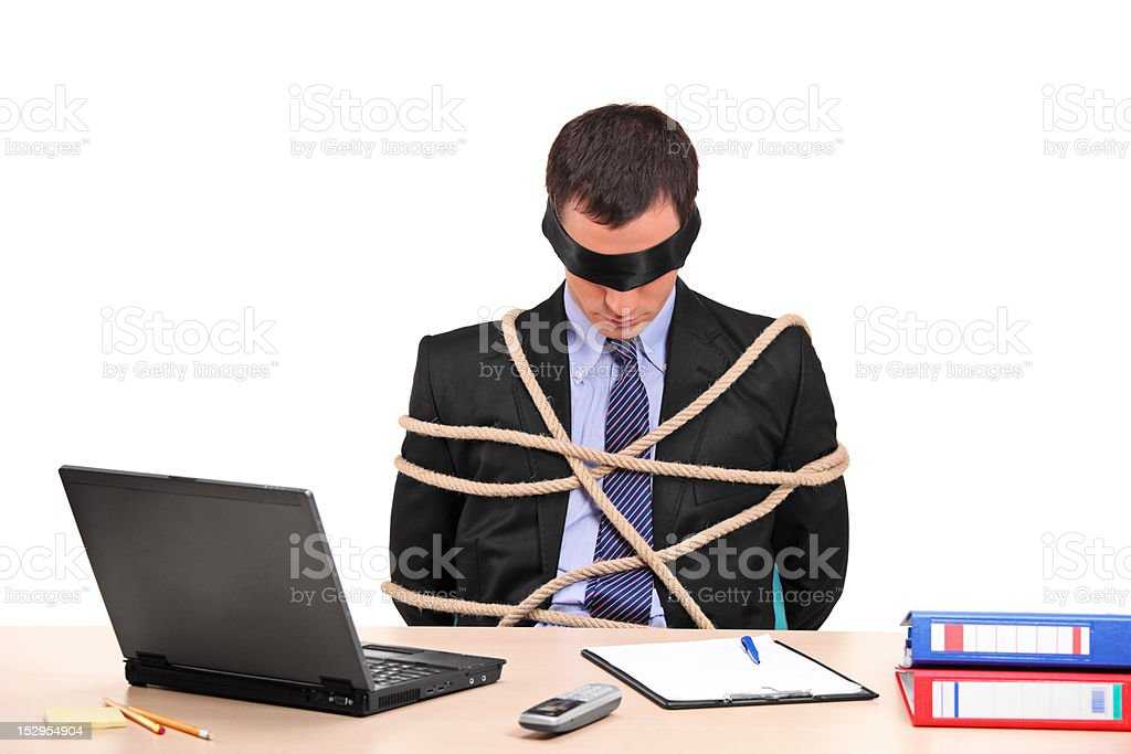 Businessman tied up with rope in his office royalty-free stock photo