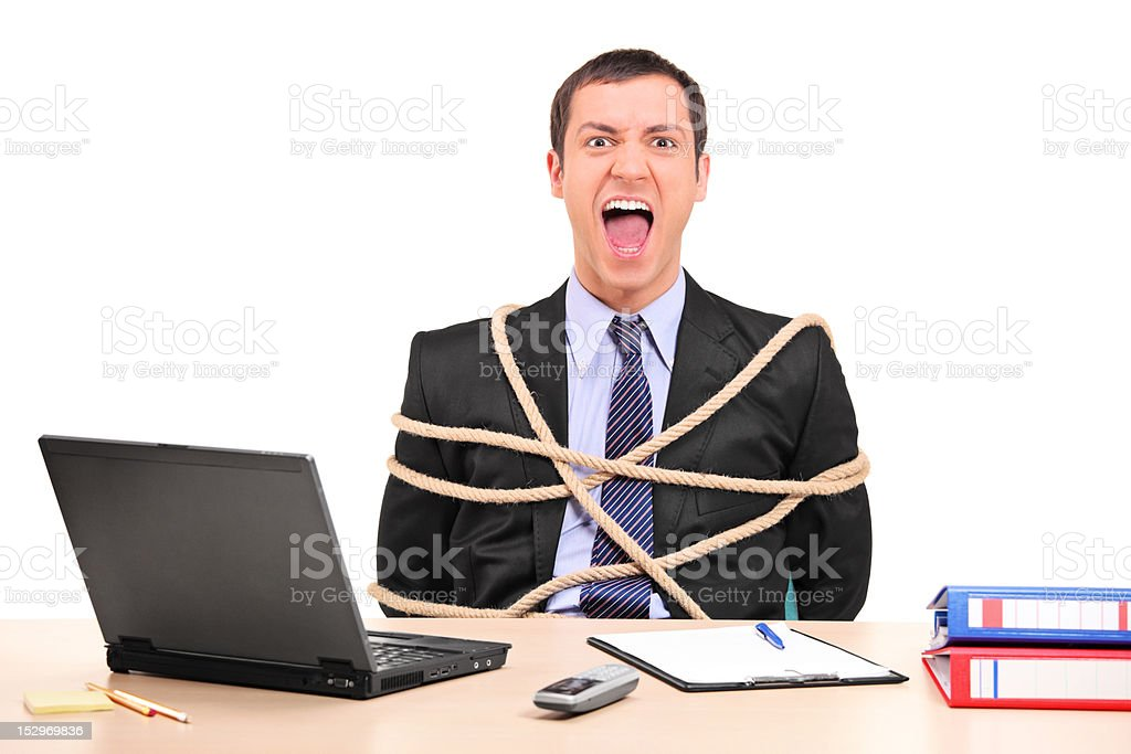 Businessman tied up with rope in the office stock photo
