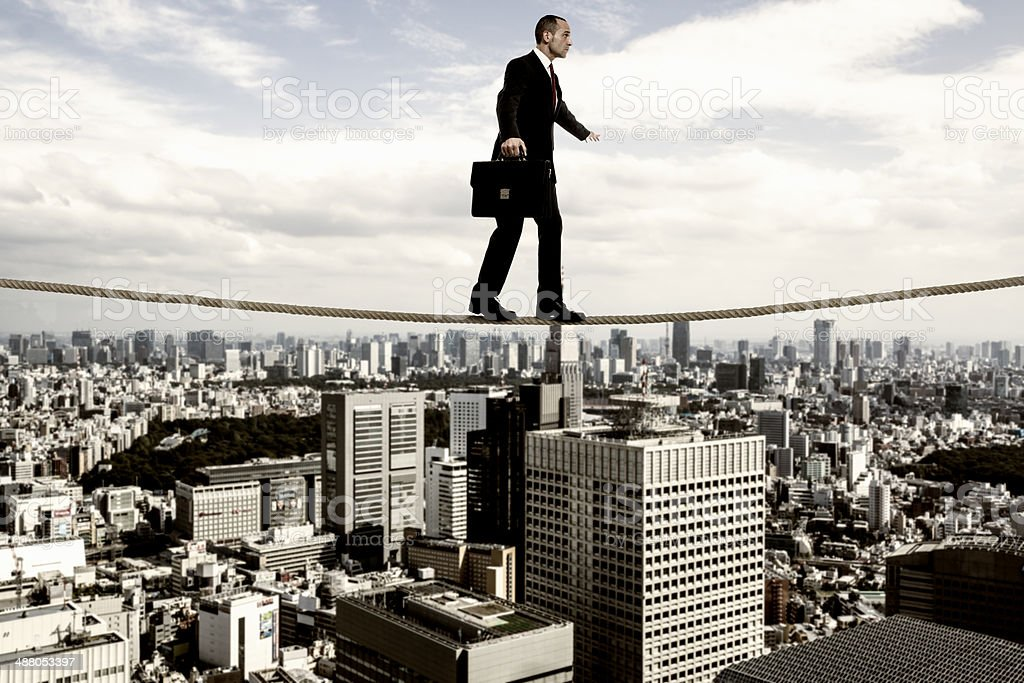 Businessman tightrope walker stock photo