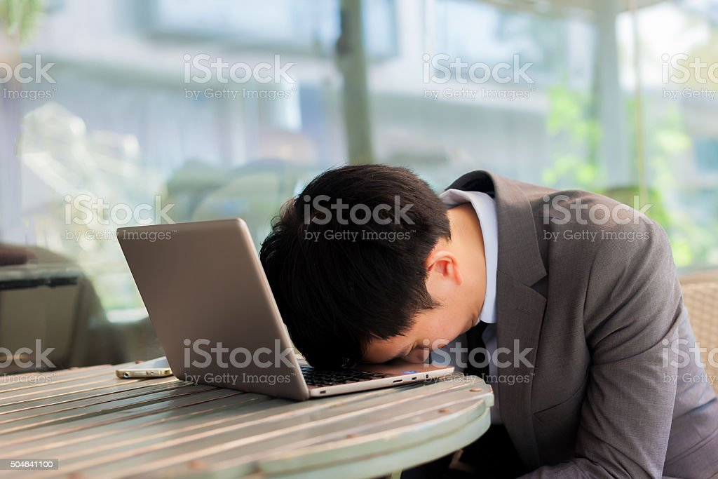 Businessman tiring and sleeping on his laptop in outdoor scene stock photo