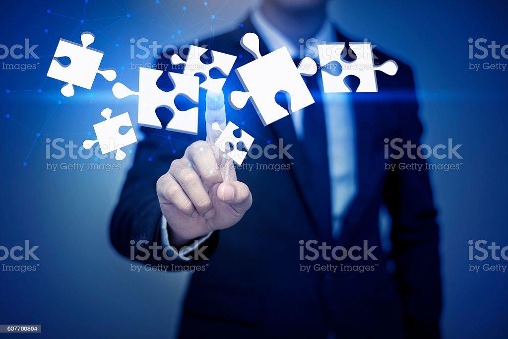 businessman touching 3D puzzle , business concept stock photo