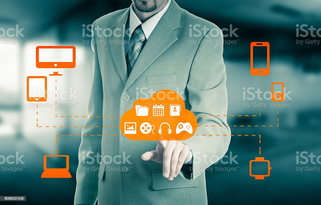 Businessman touching a cloud connected to many objects stock photo