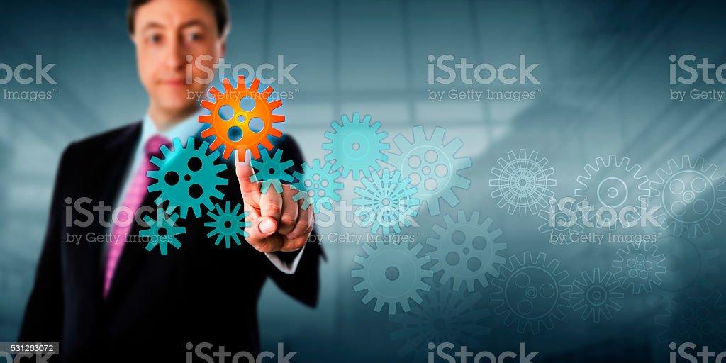 Businessman Touching Cog In A Virtual Gear Train stock photo