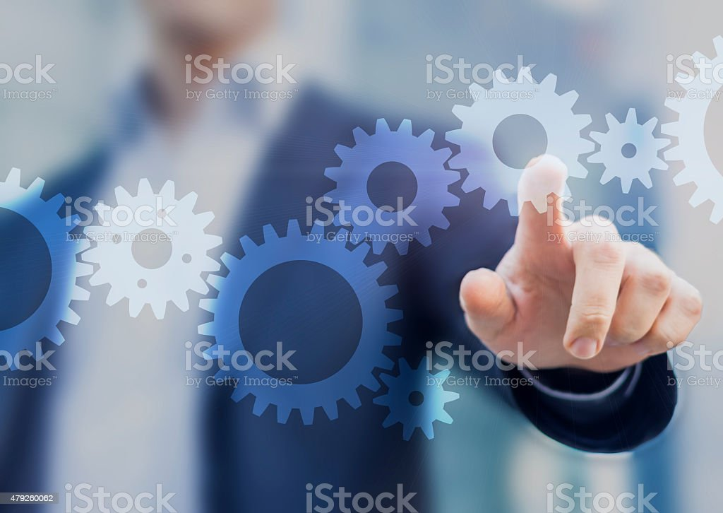 Businessman touching gears stock photo