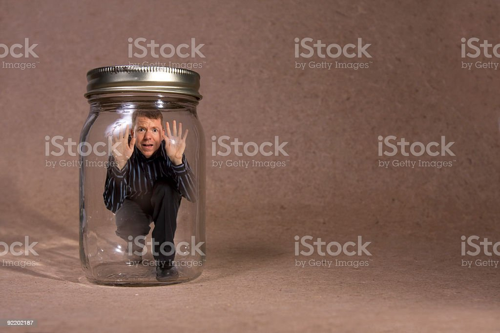 Businessman trapped in jar (Concept Series) stock photo