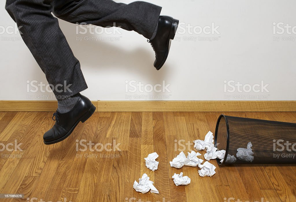 Businessman Tripping Over Wastepaper Basket stock photo