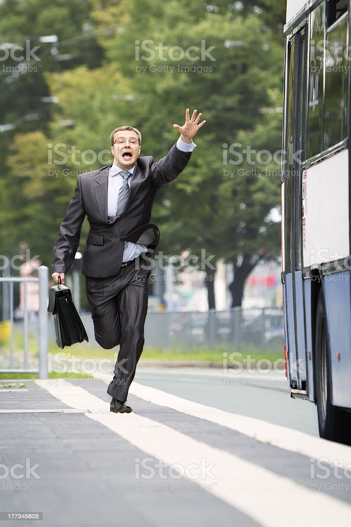 Businessman trying catch the bus stock photo