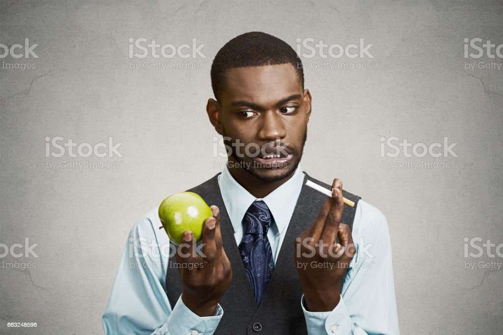 businessman trying decide on healthy life choices stock photo
