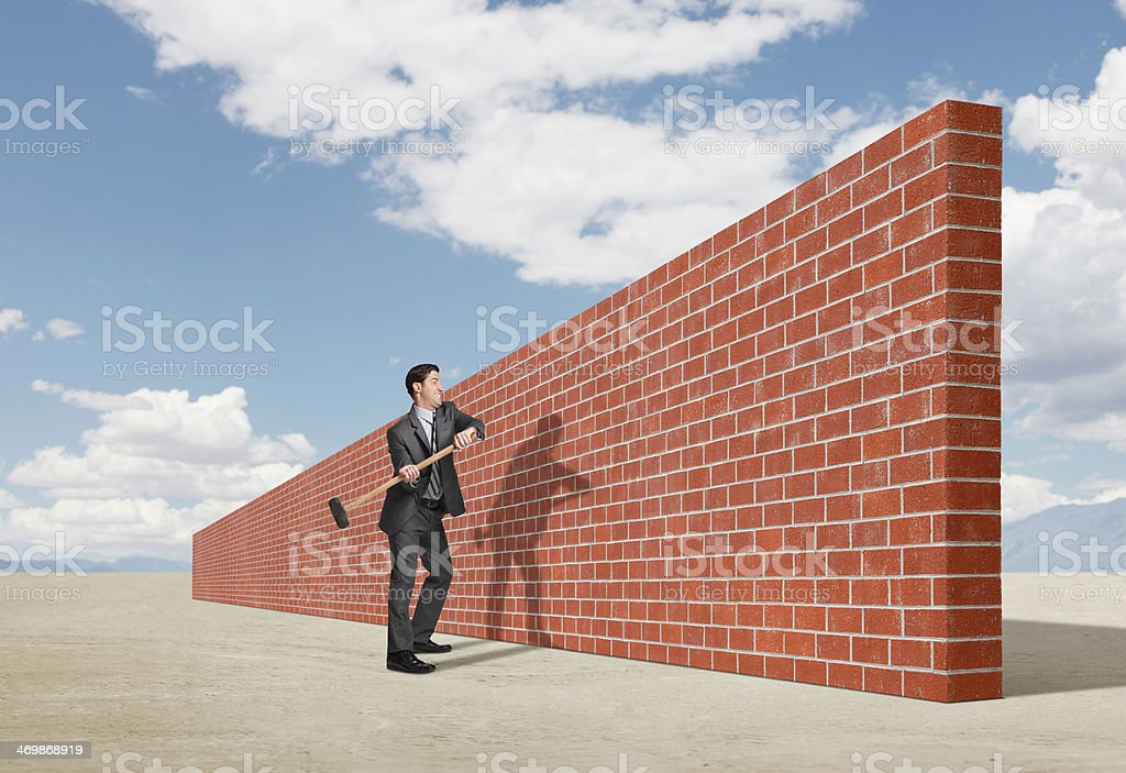 Businessman trying to break down barrier created by brick wall stock photo