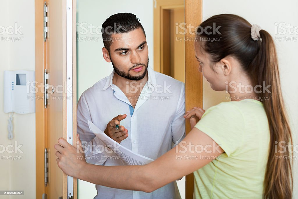 Businessman trying to collect money from housewife stock photo