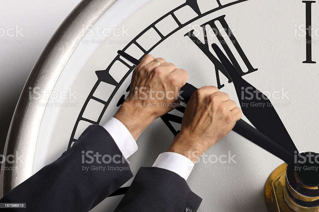 Businessman trying to hold back the hands on a clock stock photo