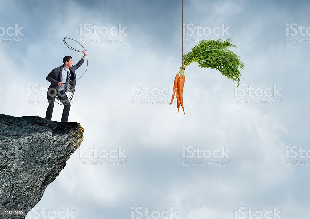 Businessman Trying To Lasso Dangling Carrots stock photo