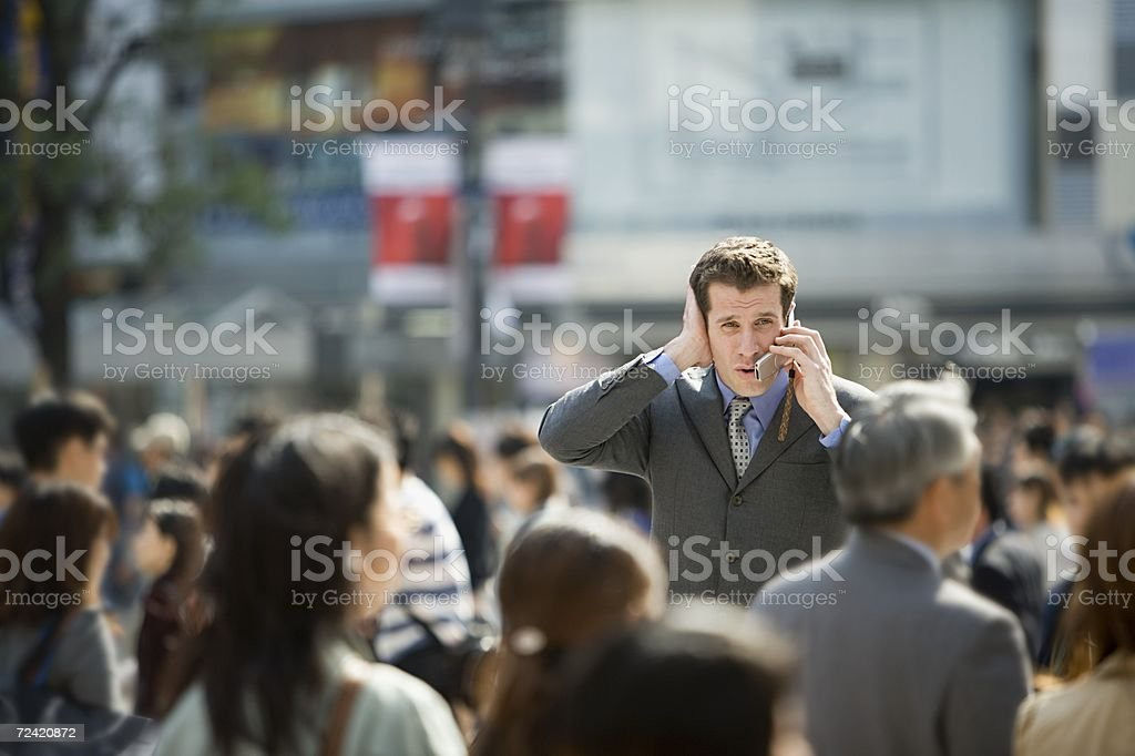 Businessman trying to listen to cell phone stock photo
