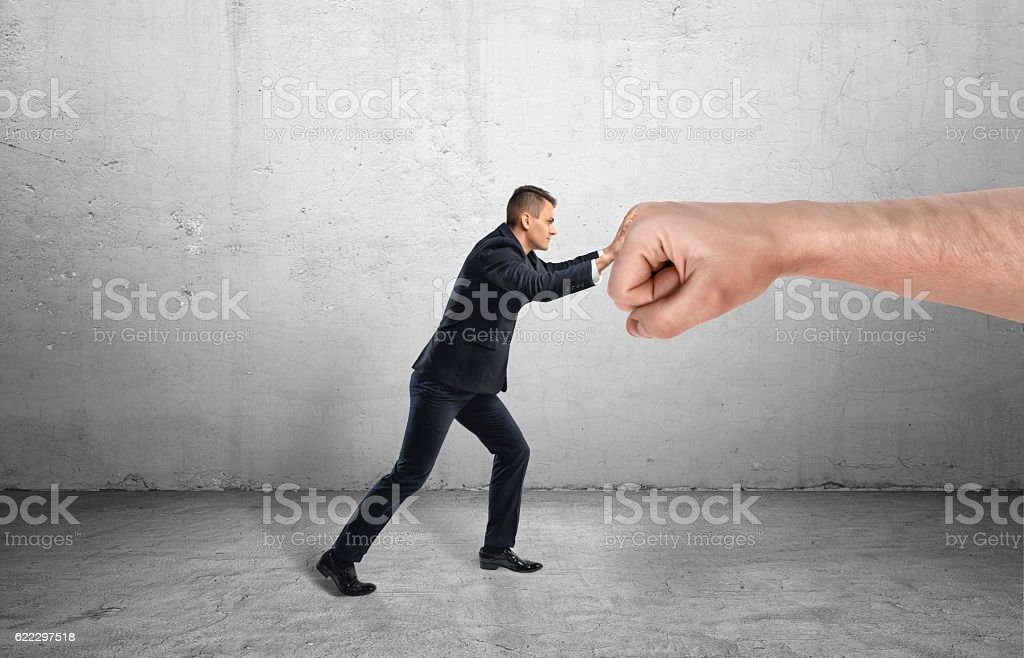 Businessman trying to resist huge male fist and move it stock photo