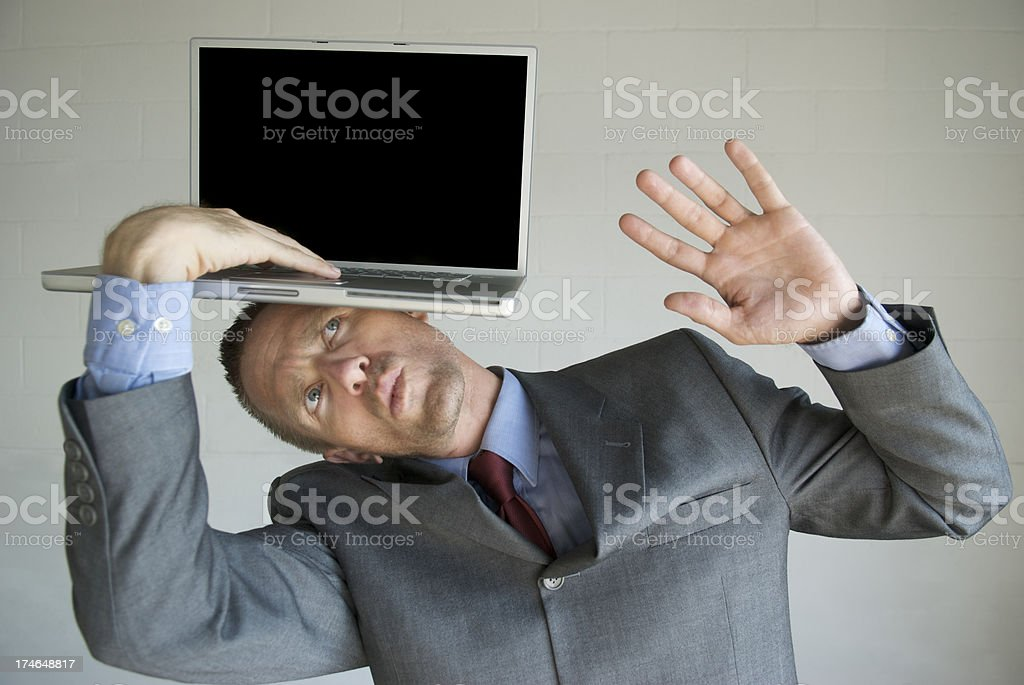 Businessman Typing on Blank Laptop Balanced on His Head royalty-free stock photo