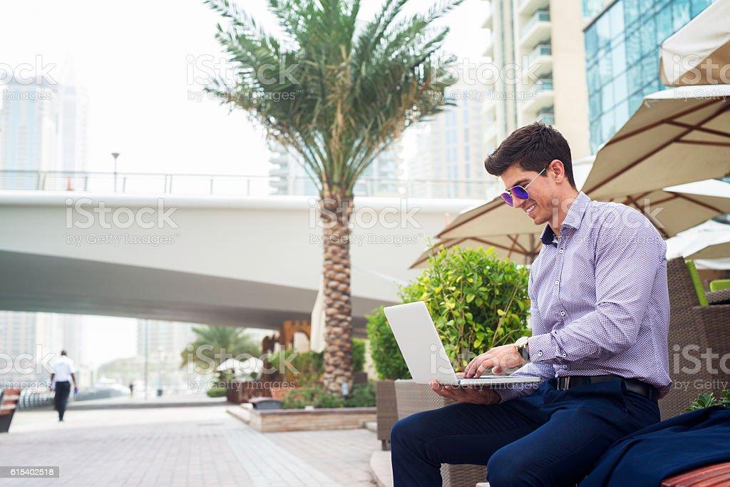 Businessman typing on laptop at Dubai Marina. stock photo