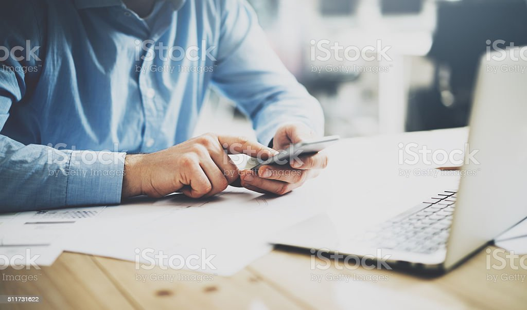 Businessman typing text smartphone. Generic design laptop on the table stock photo