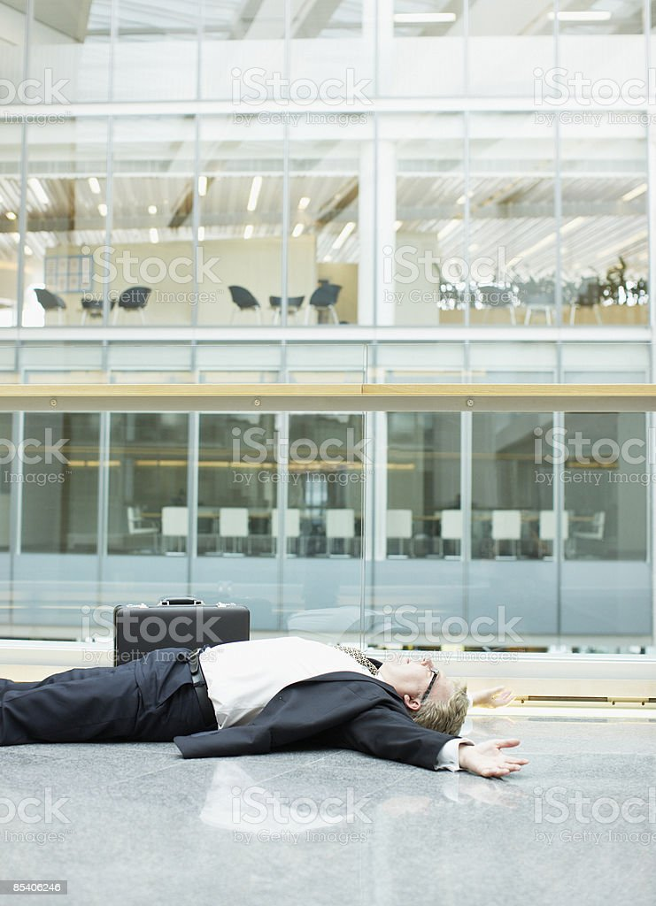 Businessman unconscious in building lobby stock photo