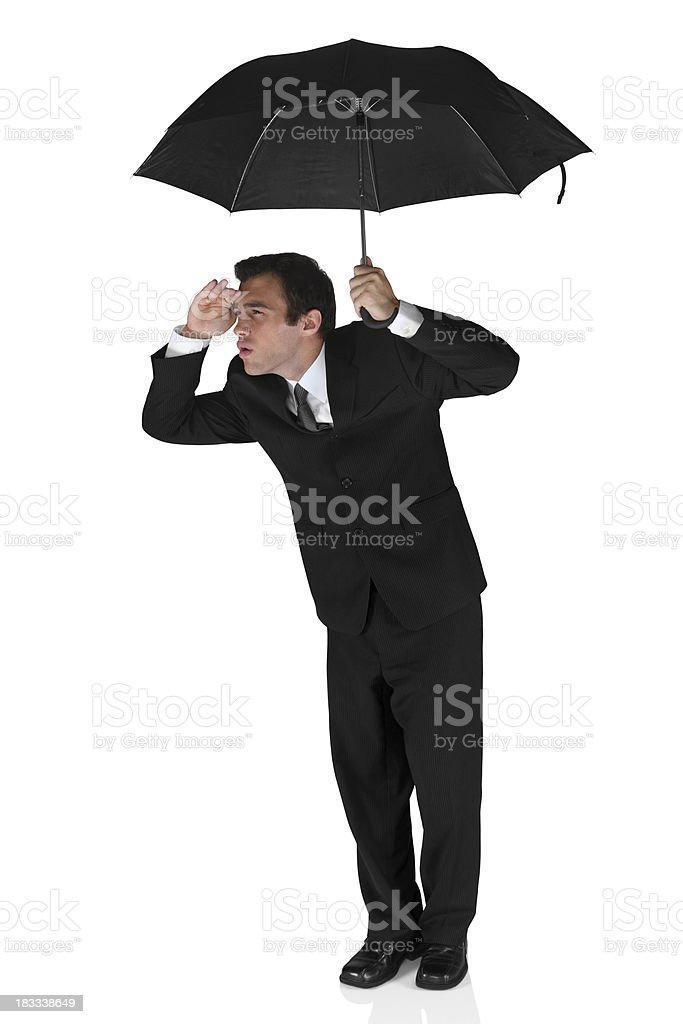 Businessman under an umbrella sheilding eyes royalty-free stock photo