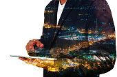 Businessman use Mobile phone with City and Communication Antenna