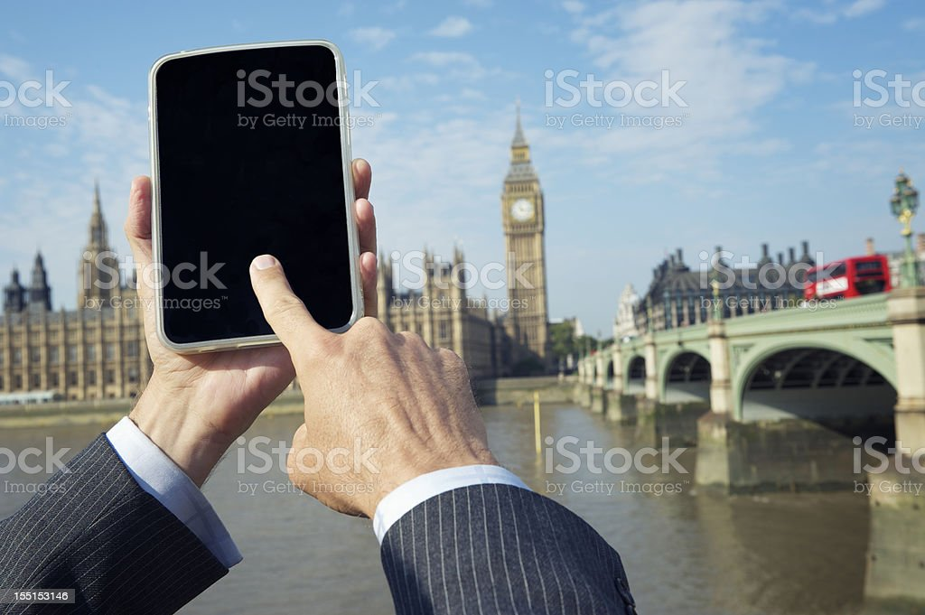 Businessman Uses Tablet Computer in front of London Skyline royalty-free stock photo