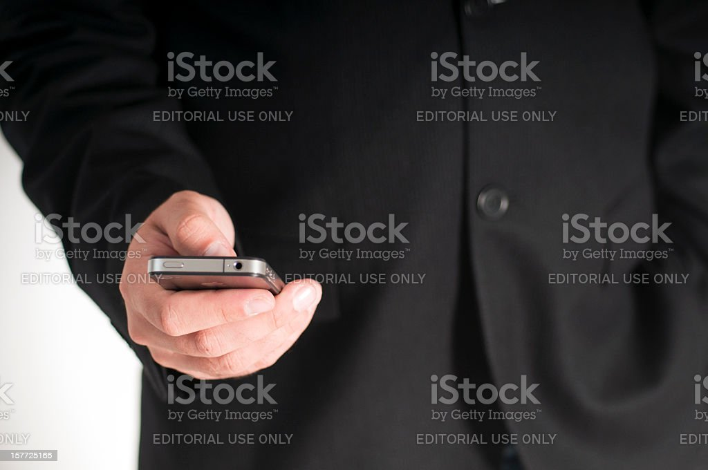 Businessman using a 4th generation Apple iPhone royalty-free stock photo