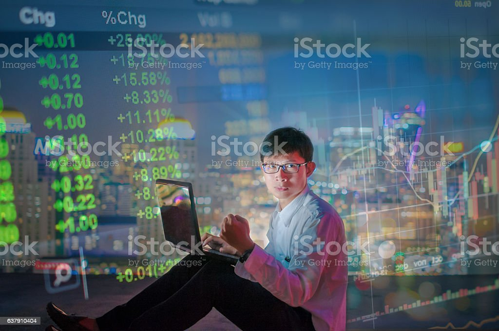 Businessman using a laptop on the rooftop of a skyscraper stock photo