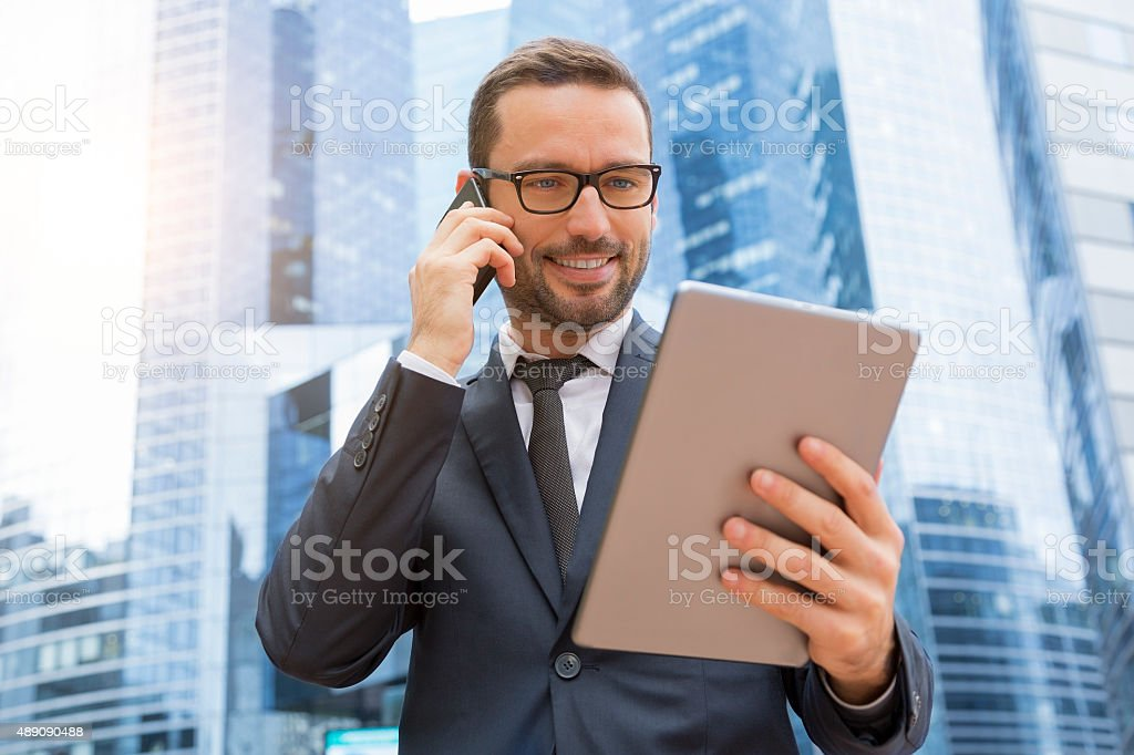 Businessman using a phone and digital tablet stock photo