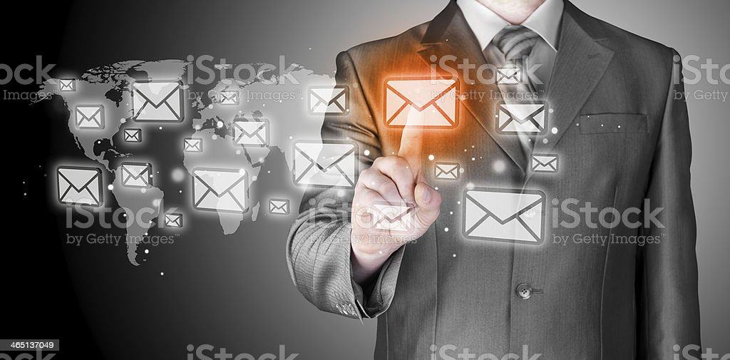 Businessman using a virtual screen to send an email stock photo
