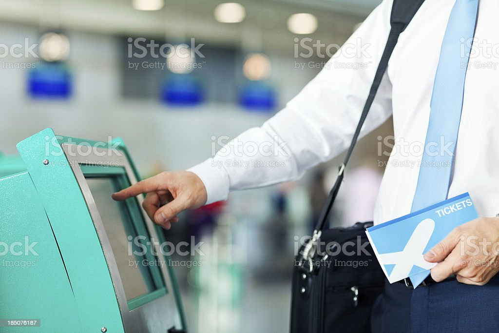 Businessman Using Automated Check In Machine At Airport stock photo