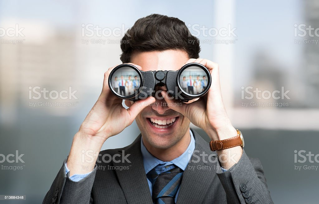 Businessman using binoculars, people portraits reflected in the lens stock photo